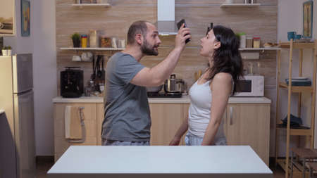 Unfaithful wife arguing to husband her guiltlessness. Jealous husband angry, frustrated, offended and irritated accusing woman of infidelity arguing her with messages on smartphone screaming desperate Foto de archivo