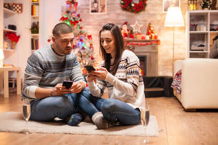 Romantic couple in matching clothes doing online shopping on their smartphone for christmas.