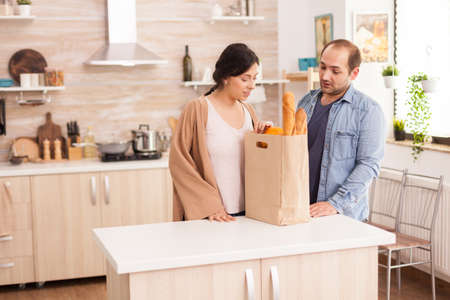 Couple looking at groceries they bought from supermarket for cooking lunch in kitchen. Healthy happy relationship lifestyle for man and woman, together shopping products Archivio Fotografico
