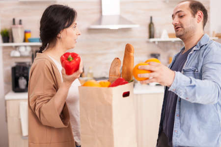 Couple with fresh groceries in paper bag from supermarket in kitchen. Healthy happy relationship lifestyle for man and woman, together shopping products Archivio Fotografico