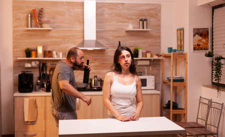 Alcoholic man screaming at beaten woman walking drunk around her in home. Violent aggressive husband abusing injuring terrified helpless, vulnerable, afraid, beaten and panicked wife. Фото со стока