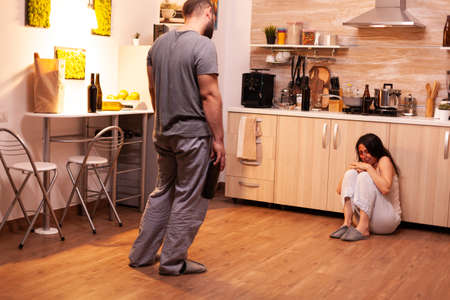 Drunk abusive husband threaten beat upset crying wife in kitchen. Traumatised helpless terrified vulnerable woman covered in bruises suffering injury from violent alcoholoic brutal husband.