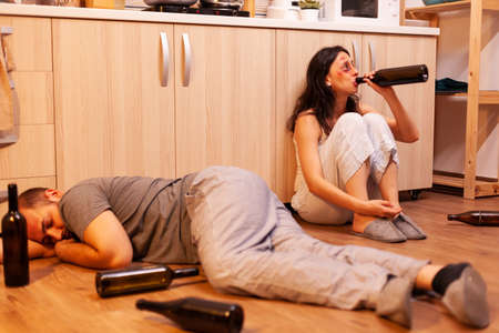 Drunk husband sleeping on kitchen floor after brutally beating his wife and being physically and psychologically affected. Aggressive man abusing injuring terrified, afraid, beaten and panicked woman . Фото со стока
