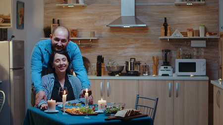 Portret of happy young couple smiling at camera sitting at the table in the kitchen during romantic dinner. Married people special tender moments, enjoyng the meal at candle lights celebration