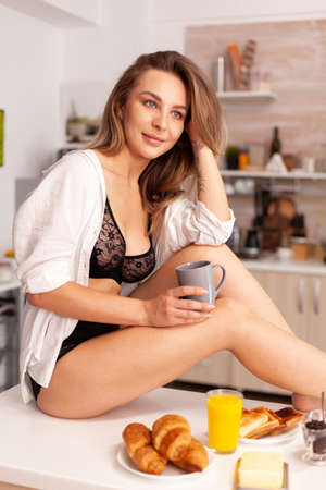 Woman enjoying coffee in the morning wearing sexy lingerie sitting on kitchen table. Provocative young woman with tattoos wearing seductive underwear.