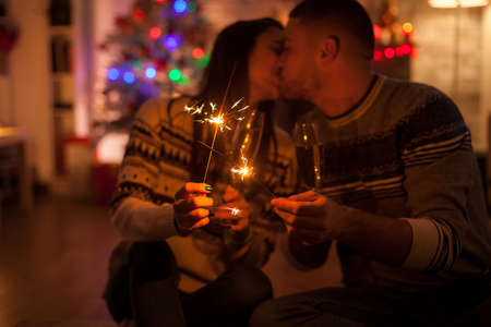 Couple kissing in dark room holding burning hand fireworks on christmas day.
