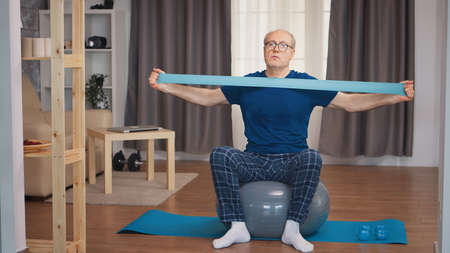Senior man in sports wear exercising with resistance band. Old person pensioner healthy training healthcare sport at home, exercising fitness activity at elderly age Фото со стока