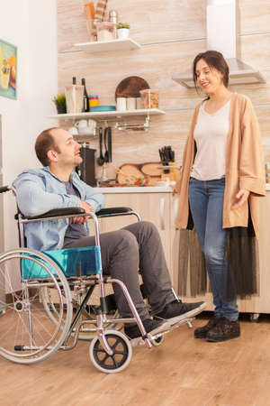 Cheerful man in wheelchair smiling at cheerful wife in kitchen. Disabled paralyzed handicapped man with walking disability integrating after an accident.