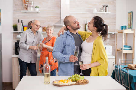 Couple looking at each other in kitchen during family brunch. Man holding glass of wine. Appetizer with various cheese.