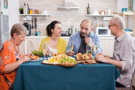 Daughter smiling at father in kitchen during family lunch. Man eating delicious food. Happy senior man at dining table. Tasty roasted potatoes. Фото со стока