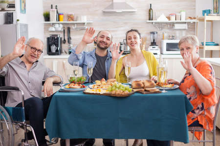 Disabled senior man in wheelchair and his family waving at camera during lunch in kitchen. Mature parents. Happy daughter and son. Фото со стока