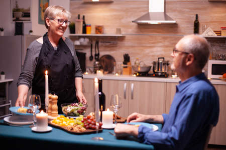 Husband sitting at dinner table and wife serving tasty food for romantic relationship anniversary. Elderly old couple talking, sitting at the table in kitchen, enjoying the meal,