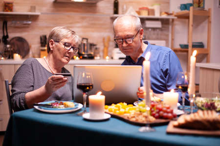 Pensioner woman using credit card to pay for romantic dinner using laptop in kitchen for her and husband. Old people sitting at the table, browsing, using the technology, internet.