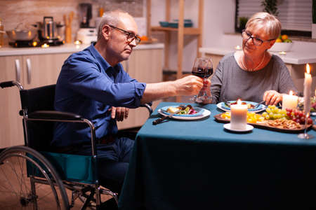Man with disabilities having dinner with wife and clinking wine glass. Wheelchair immobilized paralyzed handicapped man dining with wife at home, enjoying the meal Фото со стока
