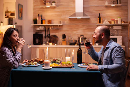 Couple enjoying a glass of wine. Happy couple talking, sitting at table in dining room, enjoying the meal, celebrating their anniversary at home having romantic time. Фото со стока