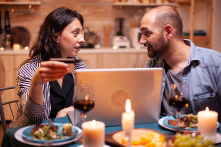 Couple looking at each other while doing online shopping during romantic dinner. Adults sitting at the table, searching, browsing, surfing, using technology card payment, internet