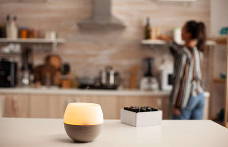 Woman cooking in kitchen and diffuser with essential oils aromatherapy on table. Aroma health essence, welness aromatherapy home spa fragrance tranquil theraphy, therapeutic steam,