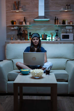 Woman freelancer in pijamas working late at night on laptop in front tv. Happy person in pijamas with eye mask sitting on sofa reading writing searching browsing on notebook using internet technology