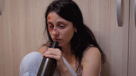 Traumatised woman drinking of sadness sitting on the floor while drunk man is sleeping. Alcoholic aggressive husband abusing injuring terrified, afraid, beaten and panicked wife living in terror.
