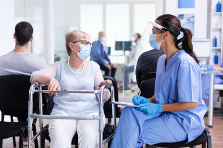 Nurse explaining diagnosis to disabled senior woman with walking frame wearing visor against infection with coronavirus in hospital hallway. Patient and medical staff in waiting area.
