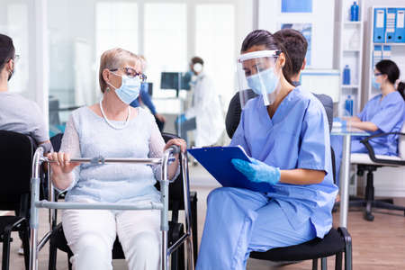 Disabled woman using walking frame in hospital waiting room wearing face mask against coronaviurs having a conversation with medical stuff. Patient and nurse in waiting area.