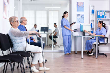 Invalid senior woman in hospital lobby with walking frame. Disabled patient in clinic for rehabilitation. Medical staff discussing about patient x-ray.