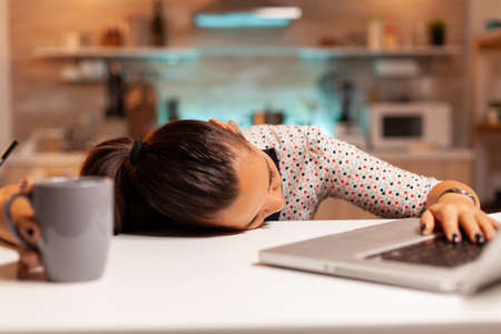 Freelance woman falling asleep in home kitchen working overtime on a project. Employee using modern technology at midnight doing overtime for job, business, busy, career, network, lifestyle ,wireless.