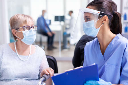 Medical staff with disabled senior woman having a conversation about recovery treatment in hospital waiting area wearing face mask against coronavirus.