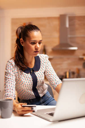 Woman holding credit card while doing online transaction using laptop in home kitchen late at night. Creative lady doing online payment using digital notebook conected to internet. 免版税图像