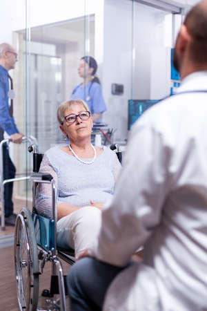 Disabled old woman sitting in wheelchair during medical examination with doctor in hospital room. Recovery treatment, help for disabled people. Elderly assistance