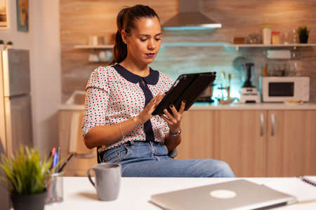 Businesswoman using tablet pc while working from home kitchen. Employee using modern technology at midnight doing overtime for job, business, busy, career, network, lifestyle ,wireless.