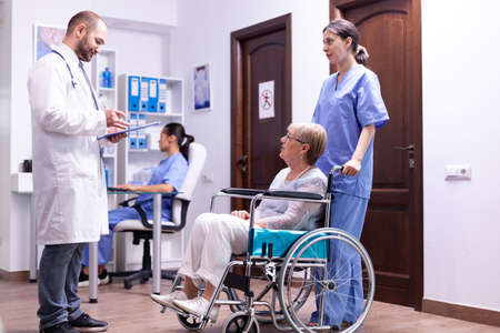 Doctor checking diagnosis of disabled senior woman in wheelchair. Medical staff in hospital hallway with invalid patient. Man in medical examination room.