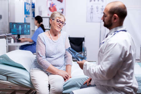 Doctor looking at patient x-ray while discussing diagnosis in hospital examination room. Healthcare medical medicinal system, disease prevention treatment, illness diagnosis