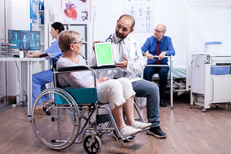 Doctor with green screen tablet in rehabilitation center for disabled patients. Man with disabilities ,walking frame sitting in hospital bed. Health care system, clinic patients.