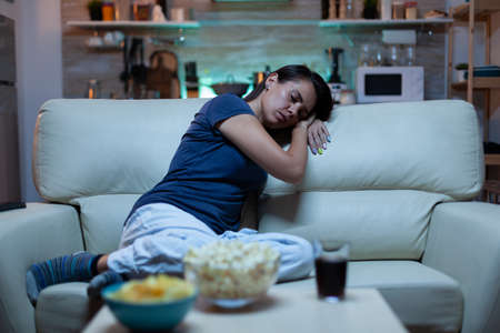 Portrait of woman sleeping on couch in living in front of television. Tired exhausted lonely sleepy lady in pajamas falling asleep sitting on cozy sofa, closing eyes while watching movie at night.