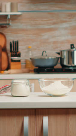 Pastry ingredients for homemade cakes and bread in empty kitchen. Modern dining room equipped with utensils ready for cooking with wheat flour in glass bowl and fresh eggs on table Stockfoto