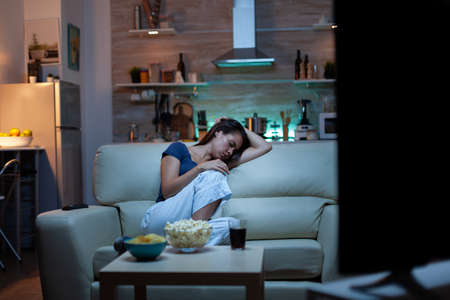 Woman sleeping on a sofa in front of TV while watching a bored movie. Tired exhausted lonely sleepy lady in pajamas falling asleep sitting on cozy couch in living room, closing eyes at night
