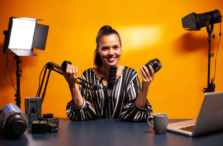 Woman smiling at camera while recording lens review for followers. New media star influencer on social media talking video photo equipment for online internet web show