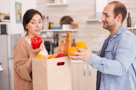 Couple taking out fresh vegetables from paper bag in kitchen after arriving home from supermarket. Healthy happy relationship lifestyle for man and woman, together shopping products Stock Photo
