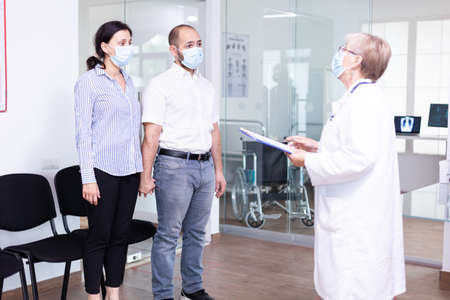 Unfavorable news from doctor to young couple in hospital waiting area during corona virus outbreak. Husband and wife wearing face mask against infection with covid 19.