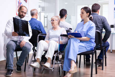 Doctor with stethoscope holding disabled senior woman radiography in wheelchair while talking with her in hospital waiting area. Patient asking about his appointment at clinic reception.