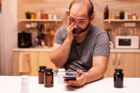 Man with pain searching on the phone medical treatment. Stressed tired unhappy worried unwell person suffering of migraine, depression, disease and anxiety feeling exhausted with dizziness symptoms