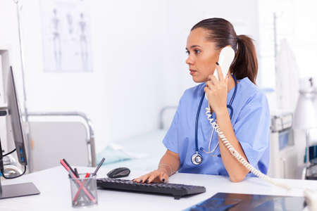 Medical nurse talking with patient on the phone about diagnosis. Health care physician sitting at desk using computer in modern clinic looking at monitor.