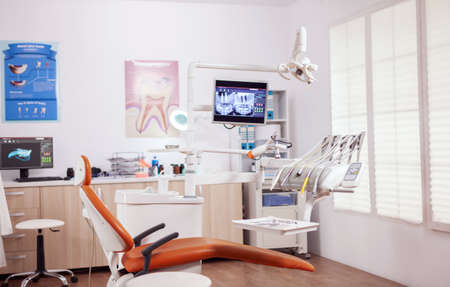 Dental chair and other accesorries used by dentist in empty cabinet. Stomatology cabinet with nobody in it and orange equipment for oral treatment.