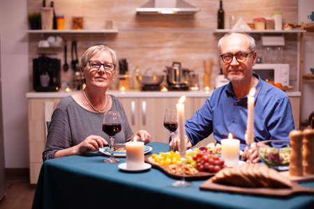 Joyful couple in kitchen looking at camera holding wine glasses looking at camera during dinner. Happy cheerful senior elderly couple dining together in the cozy kitchen, enjoying the meal.