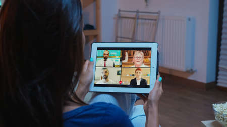 Back view of woman on videocall sitting on comfortable couch. Remote worker having online meeting consulting with colleagues on video conference and webcam chat using internet technology.