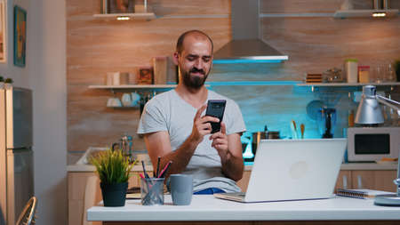 Freelancer taking break and searching on phone sitting on kitchen table working from home. Busy focused employee using modern technology network wireless doing overtime for job reading writing