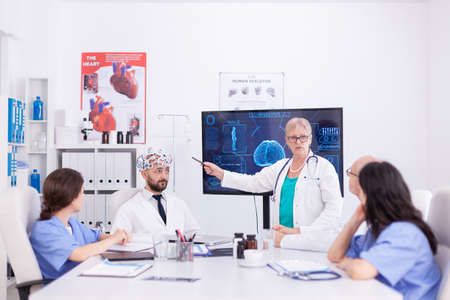 Scientist doing brain analysis using headset with sensors on doctor in hospital meeting room. Monitor shows modern brain study while team of scientist adjusts the device.