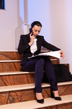 Stressed tired businesswoman readling project deadline during conversation on smartphone. Serious entrepreneur working on job project sitting on staircase of business building at night hours for job. Imagens