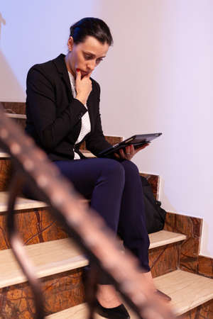 Worried stressed businesswoman reading deadline of finacial business project. Serious entrepreneur working on job project sitting on staircase of business building at night hours for job. Imagens